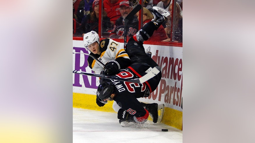 Boston Bruins' Torey Krug (47) collides with Carolina Hurricanes' Patrick Dwyer (39) during the second period of an NHL hockey game in Raleigh, N.C., Sunday, Jan. 4, 2015. (AP Photo/Karl B DeBlaker)