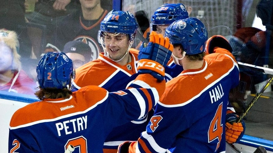 Edmonton Oilers Jeff Petry (2), Jordan Eberle (14) and Taylor Hall (4) celebrate a goal against the New York Islanders during the second period of an NHL hockey game, Sunday, Jan. 4, 2015 in Edmonton, Alberta. (AP Photo/The Canadian Press, Jason Franson)