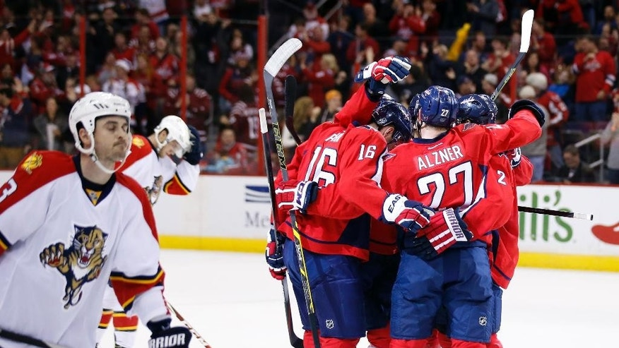 Florida Panthers center Dave Bolland skates at left as Washington Capitals right wing Eric Fehr (16), defenseman Karl Alzner (27), and defenseman Matt Niskanen (2) celebrate Alzner's goal in the second period of an NHL hockey game, Sunday, Jan. 4, 2015, in Washington. (AP Photo/Alex Brandon)