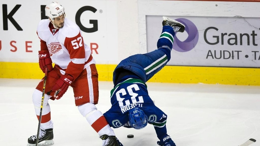 Vancouver Canucks' Henrik Sedin, right, of Sweden, is tripped up by Detroit Red Wings' Jonathan Ericsson, of Sweden, during the third period of an NHL hockey game in Vancouver, British Columbia on Saturday, Jan. 3, 2015. (AP Photo/The Canadian Press, Darryl Dyck)
