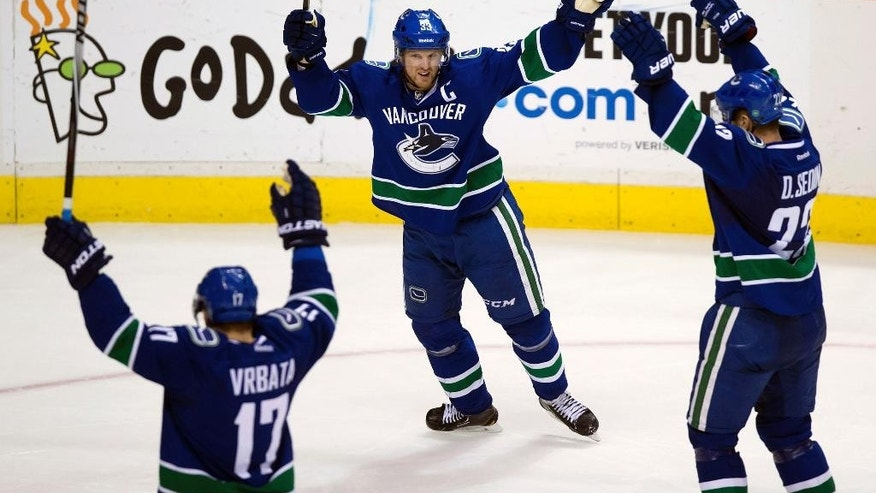 Vancouver Canucks' Radim Vrbata, of the Czech Republic, from left, Henrik Sedin, of Sweden, and Daniel Sedin, of Sweden, celebrate Vrbata's goal against the Detroit Red Wings during the third period of an NHL hockey game in Vancouver, British Columbia on Saturday, Jan. 3, 2015. (AP Photo/The Canadian Press, Darryl Dyck)