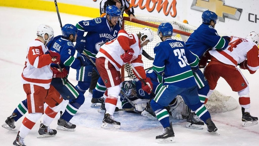 Vancouver Canucks goalie Ryan Miller, bottom center, covers up the puck as teammates Kevin Bieksa (3), Henrik Sedin, of Sweden, (33), Jannik Hansen, of Denmark, (36) and Luca Sbisa, of Switzerland, defend against the Detroit Red Wings' Riley Sheahan (15), Stephen Weiss (90) and Gustav Nyquist, of Sweden, (14) during the third period of an NHL hockey game in Vancouver, British Columbia on Saturday, Jan. 3, 2015. (AP Photo/The Canadian Press, Darryl Dyck)