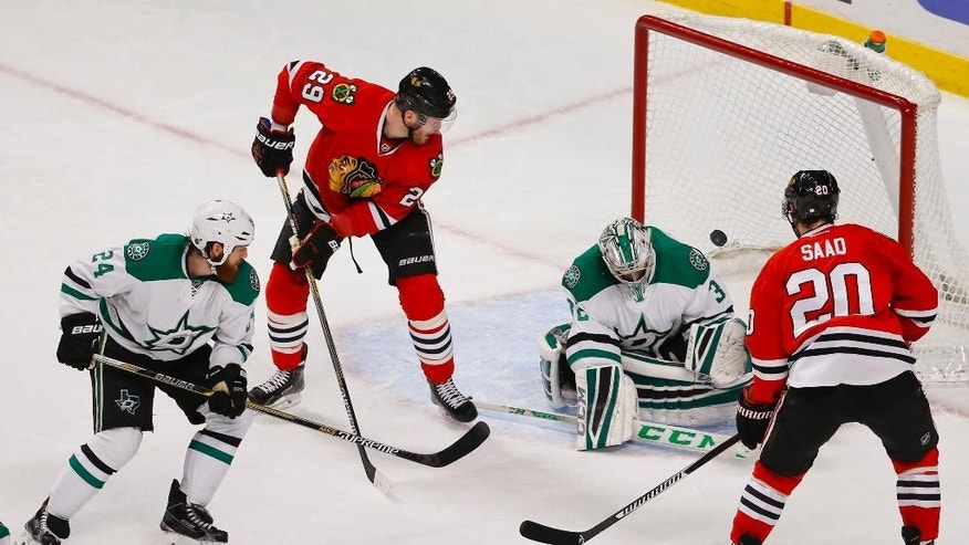 Chicago Blackhawks left wing Bryan Bickell (29) scores against Dallas Stars goalie Kari Lehtonen (32) during the second period of an NHL hockey game in Chicago, Sunday, Jan. 4, 2015. (AP Photo/Kamil Krzaczynski)