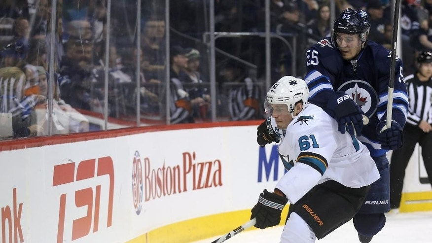 San Jose Sharks' Justin Braun (61) and Winnipeg Jets' Mark Scheifele (55) fight for the puck behind the net during the second period of an NHL hockey game Monday, Jan. 5, 2015, in Winnipeg, Manitoba. (AP Photo/The Canadian Press, Trevor Hagan)