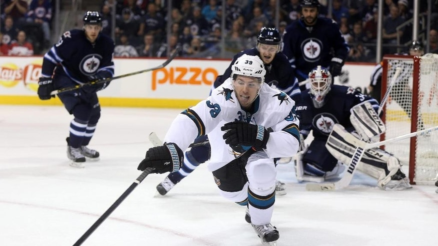 San Jose Sharks' Logan Couture (39) reaches for the puck in front of Winnipeg Jets goaltender Michael Hutchinson (34) during the first period of an NHL hockey game Monday, Jan. 5, 2015, in Winnipeg, Manitoba. (AP Photo/The Canadian Press, Trevor Hagan