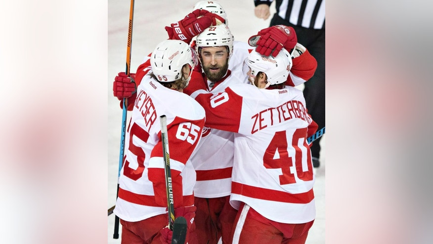 Detroit Red Wings Danny DeKeyser (65), Kyle Quincey (27) and Henrik Zetterberg (40) celebrate a goal against the Edmonton Oilers during second period NHL hockey action in Edmonton, Alberta, on Tuesday Jan. 6, 2015. (AP Photo/The Canadian Press, Jason Franson)