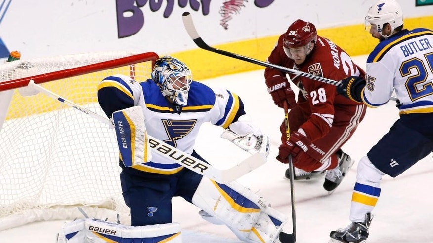 St. Louis Blues' Brian Elliott, left, makes a save on a shot as Arizona Coyotes' Lauri Korpikoski (28), of Finland, moves in for a possible rebound as Blues' Chris Butler, right, defends during the second period of an NHL hockey game Tuesday, Jan. 6, 2015, in Glendale, Ariz. (AP Photo/Ross D. Franklin)