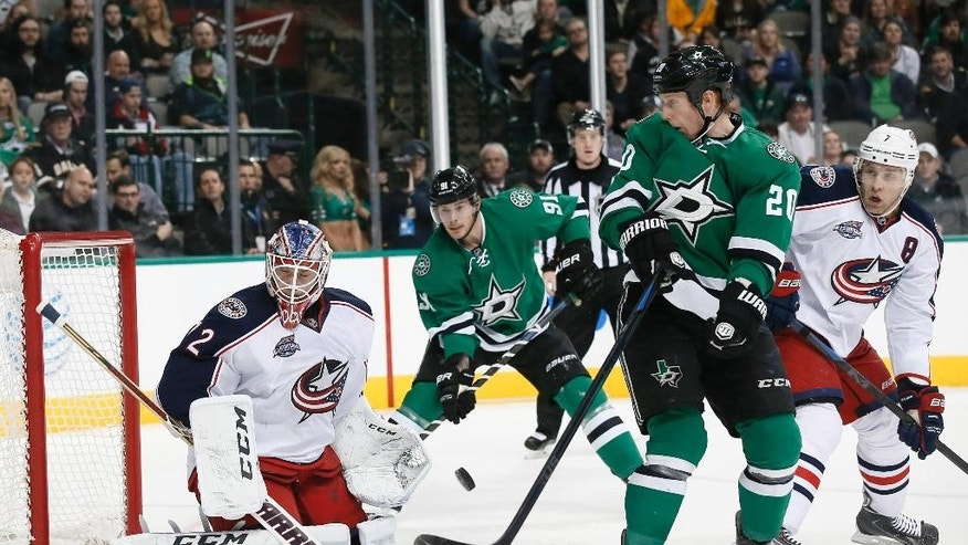 Dallas Stars center Cody Eakin (20) looks back to see Columbus Blue Jackets' Sergei Bobrovsky (72) of Russia defend against an airborne puck in the first period of an NHL hockey game, Tuesday, Jan. 6, 2015, in Dallas. The Stars' Tyler Seguin (91) and the Blue Jackets' Jack Johnson (7) watch the play. (AP Photo/Tony Gutierrez)