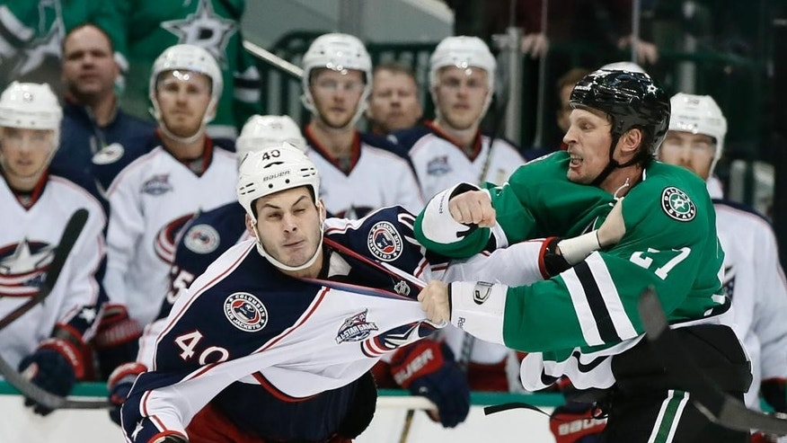 Columbus Blue Jackets' Jared Boll (40) recoils from a punch to the side of the head by Dallas Stars' Travis Moen (27) during a fight in the second period of an NHL hockey game, Tuesday, Jan. 6, 2015, in Dallas. (AP Photo/Tony Gutierrez)