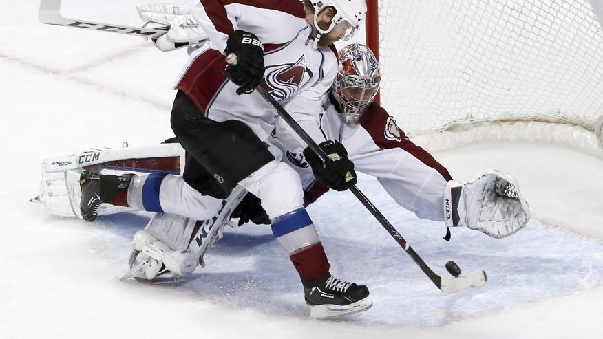 Colorado Avalanche goalie Semyon Varlamov gets defensive help from Brad Stuart (17) during the second period of an NHL hockey game against the Chicago Blackhawks Tuesday, Jan. 6, 2015, in Chicago. (AP Photo/Charles Rex Arbogast)