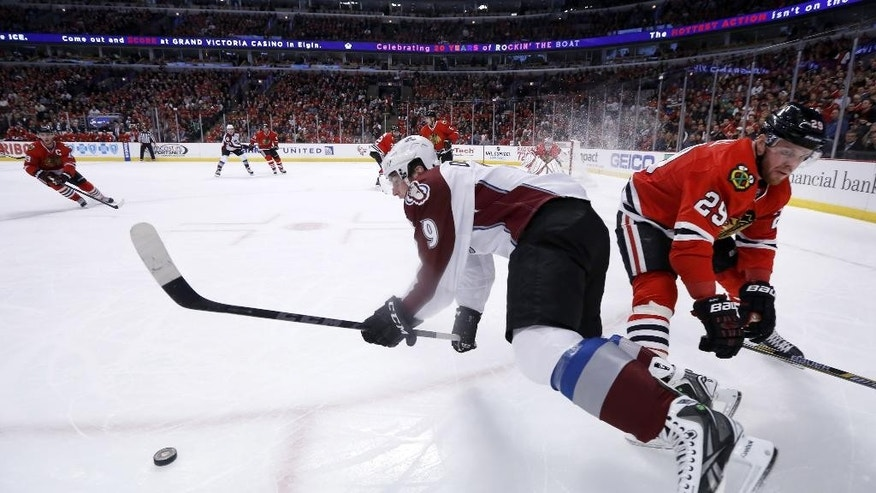Chicago Blackhawks left wing Bryan Bickell (29) checks Colorado Avalanche center Matt Duchene (9) near the boards during the first period of an NHL hockey game Tuesday, Jan. 6, 2015, in Chicago. (AP Photo/Charles Rex Arbogast)