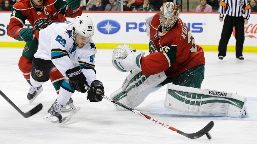 San Jose Sharks left wing Barclay Goodrow (89) dives for the puck in front of Minnesota Wild center Mikko Koivu, left, of Finland, as Wild goalie Darcy Kuemper, right, defends without his stick during the second period of an NHL hockey game in St. Paul, Minn., Tuesday, Jan. 6, 2015. (AP Photo/Ann Heisenfelt)