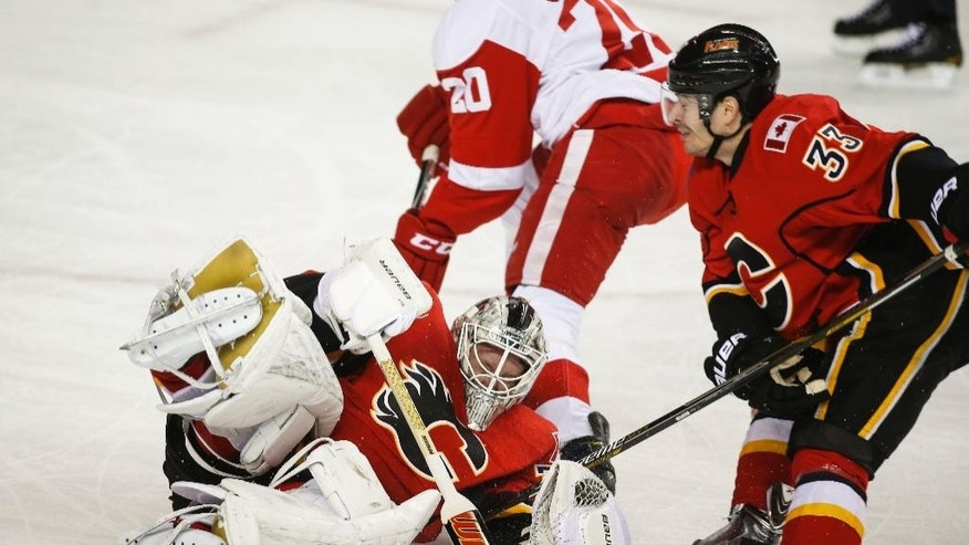 Detroit Red Wings' Drew Miller, center, has the puck stolen from him by Calgary Flames goalie Karri Ramo, bottom, from Finland, as Flames' Raphael Diaz, from Switzerland, tries to avoid Ramo during second-period NHL hockey game action in Calgary, Alberta, Wednesday, Jan. 7, 2015. (AP Photo/The Canadian Press, Jeff McIntosh)