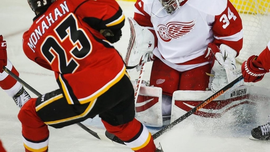 Detroit Red Wings goalie Petr Mrazek, right, from the Czech Republic, deflects a shot from Calgary Flames' Sean Monahan during second-period NHL hockey game action in Calgary, Alberta, Wednesday, Jan. 7, 2015. (AP Photo/The Canadian Press, Jeff McIntosh)