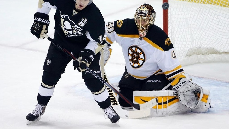 Pittsburgh Penguins' Chris Kunitz (14) deflects the puck over Boston Bruins goalie Tuukka Rask (40) and wide of the net during the first period of an NHL hockey game in Pittsburgh Wednesday, Jan. 7, 2015.(AP Photo/Gene J. Puskar)