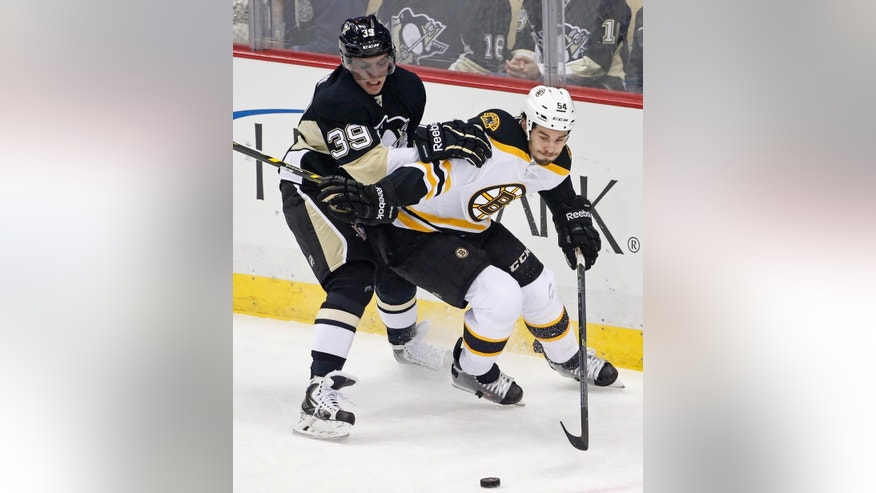 Pittsburgh Penguins' David Perron (39) and Boston Bruins' Adam McQuaid (54) vie for the puck during the first period of an NHL hockey game in Pittsburgh on Wednesday, Jan. 7, 2015.(AP Photo/Gene J. Puskar)