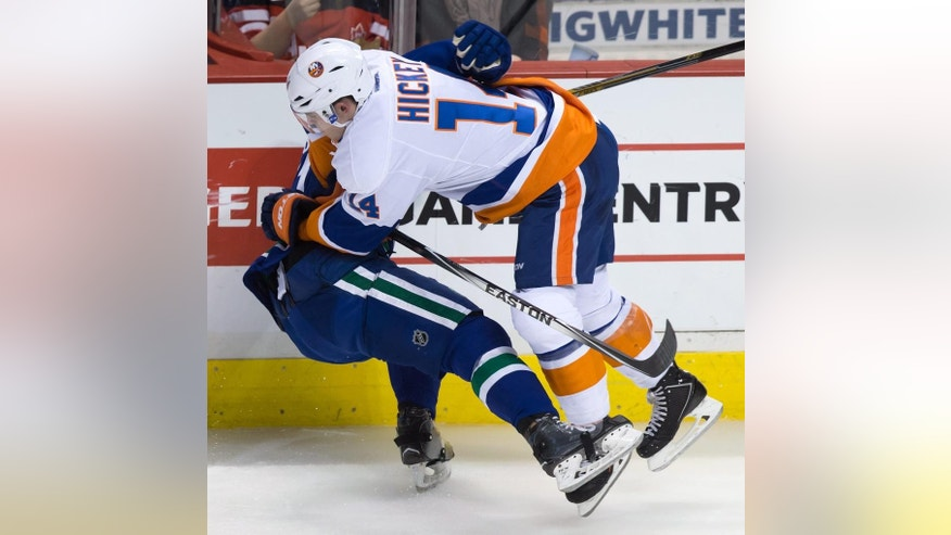 New York Islanders' Thomas Hickey, right, checks Vancouver Canucks' Derek Dorsett during the second period of an NHL hockey game Tuesday, Jan. 6, 2015, in Vancouver, British Columbia. (AP Photo/The Canadian Press, Darryl Dyck)