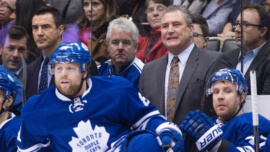 Toronto Maple Leafs new interim head coach Peter Horachek, center, looks on as Maple Leafs' Phil Kessel, left, jumps on the ice against the Washington Capitals during the first period of an NHL hockey game, Wednesday, Jan. 7, 2015 in Toronto. (AP Photo/The Canadian Press, Nathan Denette)