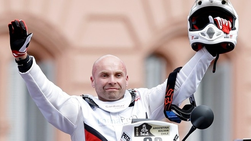 In this Sunday, Jan. 4 photo, Michal Hernik of Poland posses for a picture as he crosses the podium ramp during the symbolic start of the Dakar Rally 2015 in Buenos Aires, Argentina, 2015. According to race authorities Hernik was found dead during the third stage of the race between the cities of San Juan and Chilecito, in Argentina, Tuesday Jan. 6, 2015.