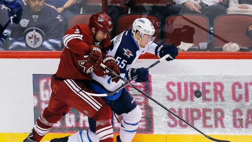 Arizona Coyotes center Kyle Chipchura (24), left, and Winnipeg Jets center Mark Scheifele (55) battle for the puck in the second period during an NHL hockey game, Thursday, Jan. 8, 2015, in Glendale, Ariz. (AP Photo/Rick Scuteri)