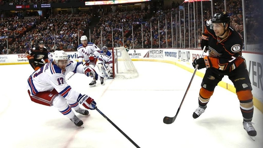 Anaheim Ducks center Andrew Cogliano fires a pass past New York Rangers defenseman John Moore during the second period of an NHL hockey game Wednesday, Jan. 7, 2015, in Anaheim, Calif. (AP Photo/Lenny Ignelzi)