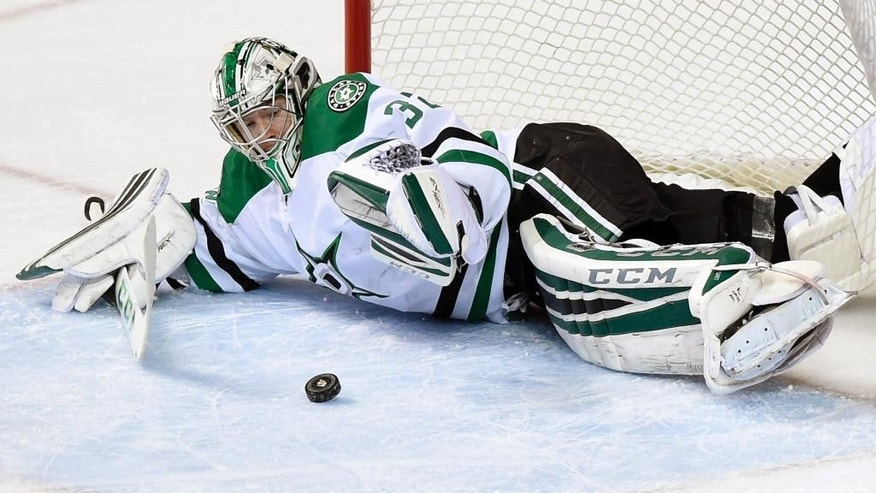 Dallas Stars goalie Kari Lehtonen (32), of Finland, brings his glove down onto the puck against the Nashville Predators in the first period of an NHL hockey game Thursday, Jan. 8, 2015, in Nashville, Tenn. (AP Photo/Sanford Myers)