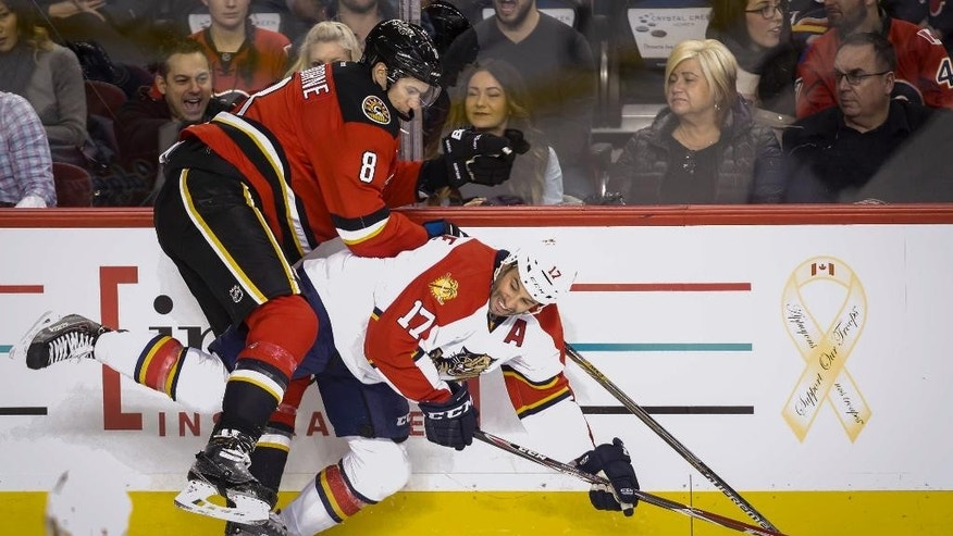 Florida Panthers' Derek MacKenzie, right, is checked by Calgary Flames' Joe Colborne during the second period of an NHL hockey game Friday, Jan. 9, 2015, in Calgary, Alberta. (AP Photo/The Canadian Press, Jeff McIntosh)
