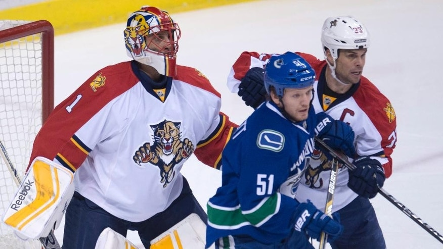 Florida Panthers goalie Roberto Luongo (1) keeps his eye on the play as Panthers defenseman Willie Mitchell (33) tries to clear Vancouver Canucks right wing Derek Dorsett (51) from in front of the net during first-period NHL hockey game action in Vancouver, British Columbia, Thursday, Jan. 8, 2015. (AP Photo/The Canadian Press, Jonathan Hayward)