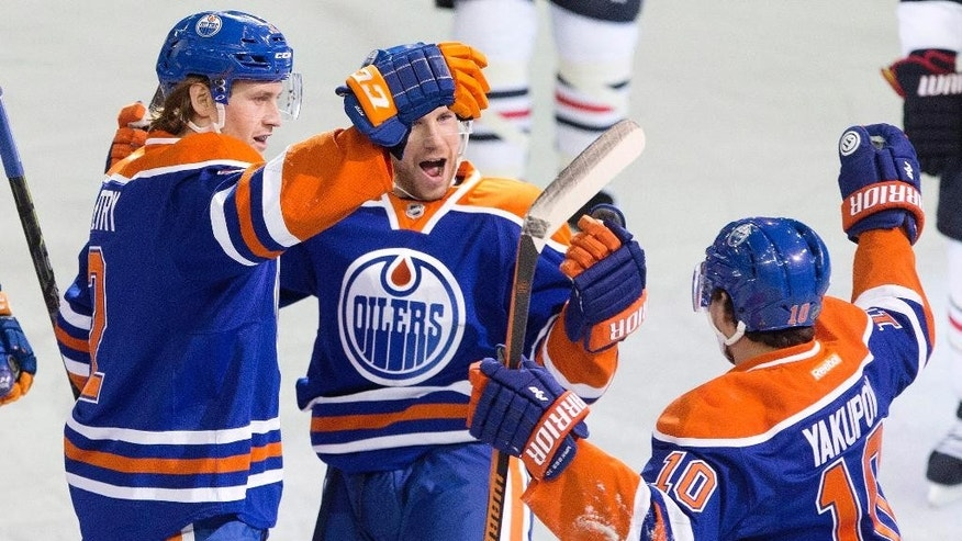 Edmonton Oilers' Jeff Petry (2), Derek Roy (8) and Nail Yakupov (10) celebrate a goal against the Chicago Blackhawks during the second period of an NHL hockey game Friday, Jan. 9, 2015, in Edmonton, Alberta. (AP Photo/The Canadian Press, Jason Franson)