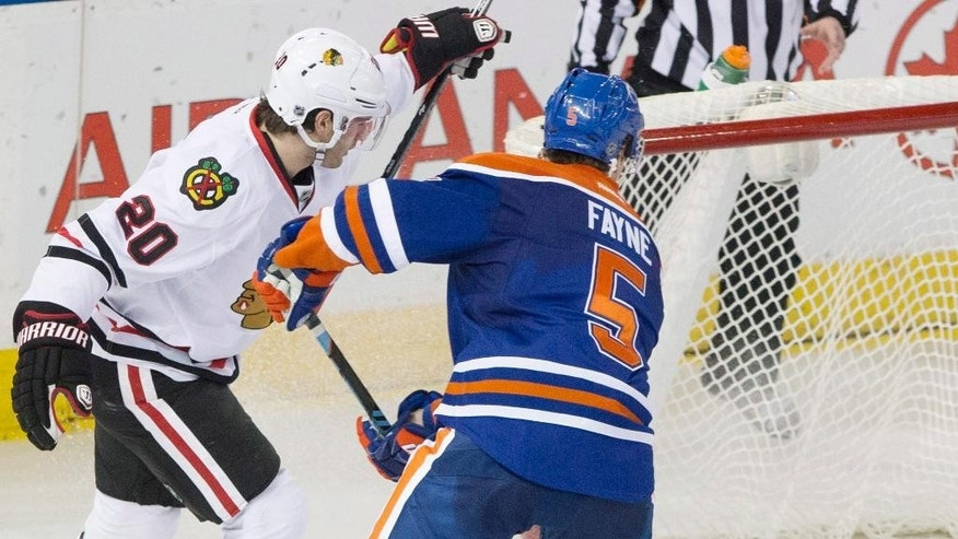 Chicago Blackhawks' Brandon Saad (20) watches the puck go in the net as Edmonton Oilers' Mark Fayne (5) tries to defend during the second period of an NHL hockey game Friday, Jan. 9, 2015, in Edmonton, Alberta. (AP Photo/The Canadian Press, Jason Franson)