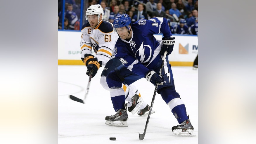 Tampa Bay Lightning right wing Brett Connolly (14) skates past Buffalo Sabres defenseman Andre Benoit (61) during the second period of an NHL hockey game Friday, Jan. 9, 2015, in Tampa, Fla. (AP Photo/Chris O'Meara)