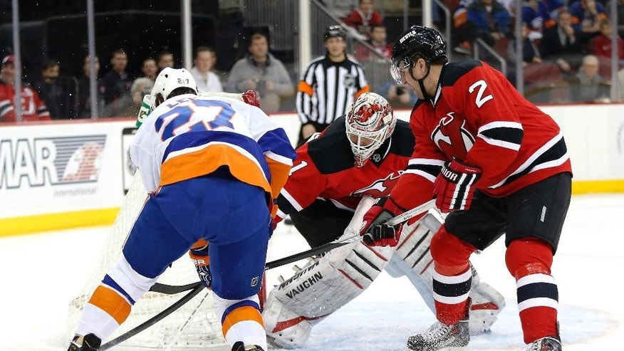 New York Islanders center Anders Lee, left, attacks against New Jersey Devils goalie Keith Kinkaid, center, and defenseman Marek Zidlicky, of the Czech Republic, during the first period of an NHL hockey game, Friday, Jan. 9, 2015, in Newark, N.J. (AP Photo/Julio Cortez)