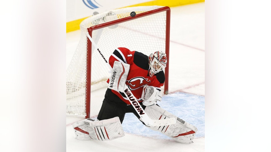 New Jersey Devils goalkeeper Keith Kinkaid (1) deflects a New York Islanders shot during the third period of an NHL hockey game, Friday, Jan. 9, 2015, in Newark, N.J. (AP Photo/Julio Cortez)