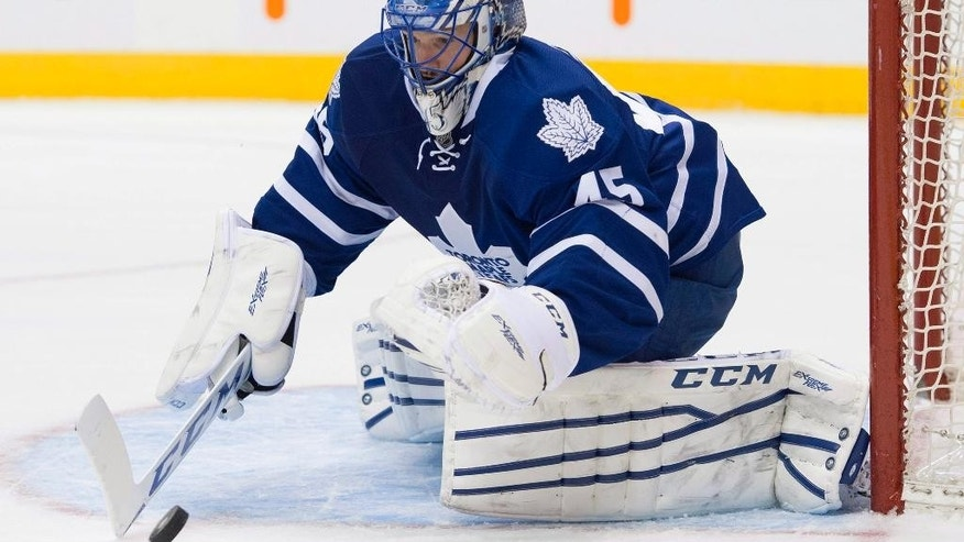 Toronto Maple Leafs goaltender Jonathan Bernier covers the puck after making a save against the Columbus Blue Jackets during the first period of an NHL hockey game Friday, Jan. 9, 2015, in Toronto. (AP Photo/The Canadian Press, Darren Calabrese)
