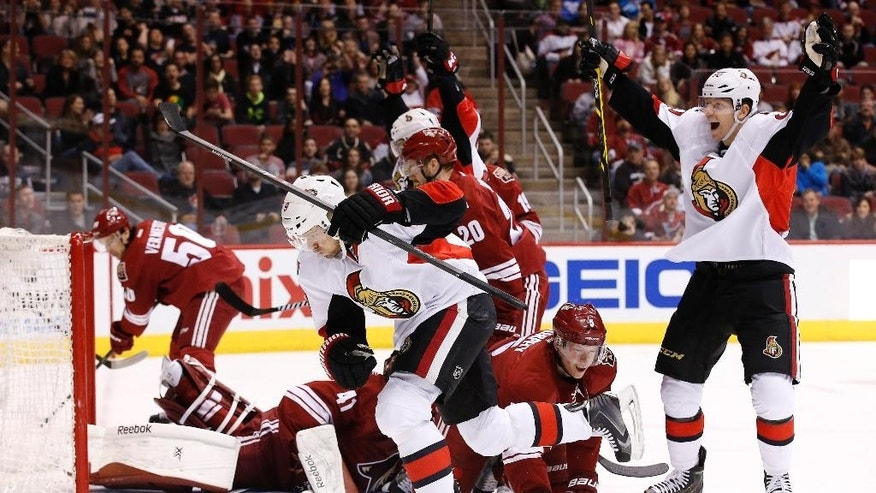 Ottawa Senators' Milan Michalek (9), of the Czech Republic, celebrates his goal against the Arizona Coyotes as teammate Alex Chiasson, right, celebrates while Coyotes' Connor Murphy (5) kneels on the ice during the first period of an NHL hockey game Saturday, Jan. 10, 2015, in Glendale, Ariz.  (AP Photo/Ross D. Franklin)