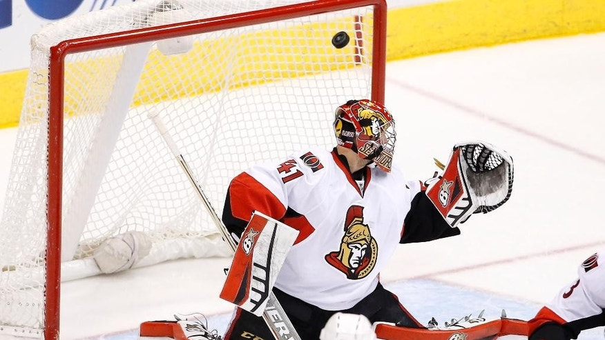 Ottawa Senators' Craig Anderson watches the puck get past him on a shot by the Arizona Coyotes during the second period of an NHL hockey game Saturday, Jan. 10, 2015, in Glendale, Ariz.  The puck did not go into the net but instead it bounced around the front along the goal line. (AP Photo/Ross D. Franklin)