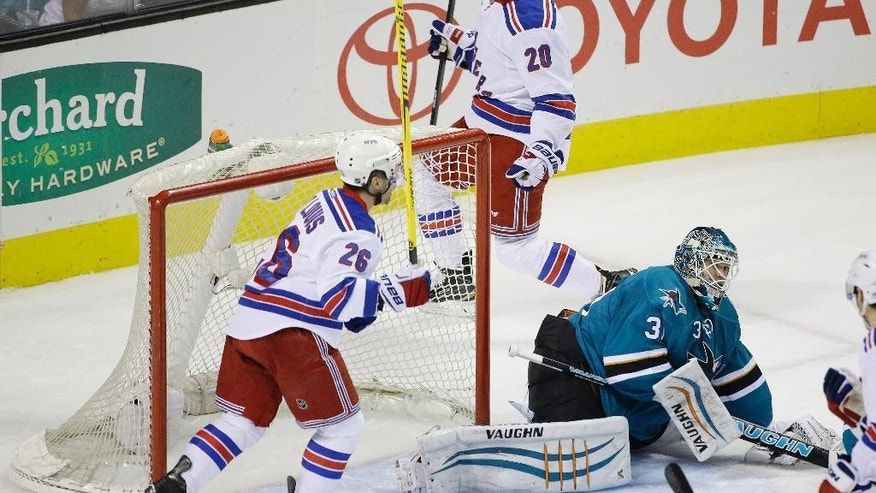 New York Rangers' Chris Kreider, center, celebrates his goal past San Jose Sharks goalie Antti Niemi, bottom right, during the first period of an NHL hockey game Saturday, Jan. 10, 2015, in San Jose, Calif. (AP Photo/Marcio Jose Sanchez)