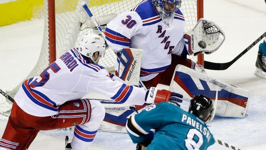 New York Rangers goalie Henrik Lundqvist, top, stops a shot by San Jose Sharks' Joe Pavelski (8) during the second period of an NHL hockey game Saturday, Jan. 10, 2015, in San Jose, Calif. (AP Photo/Marcio Jose Sanchez)