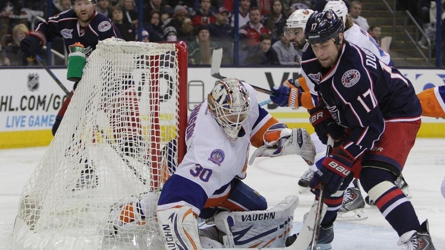 New York Islanders' Chad Johnson, left, makes a save against Columbus Blue Jackets' Brandon Dubinsky during the second period of an NHL hockey game Saturday, Jan. 10, 2015, in Columbus, Ohio. (AP Photo/Jay LaPrete)