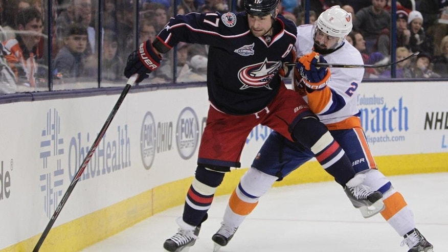 New York Islanders' Nick Leddy, right, checks Columbus Blue Jackets' Brandon Dubinsky during the second period of an NHL hockey game Saturday, Jan. 10, 2015, in Columbus, Ohio. (AP Photo/Jay LaPrete)