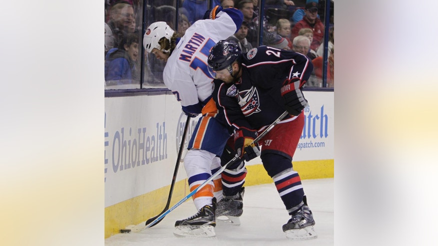 New York Islanders' Matt Martin, left, and Columbus Blue Jackets' James Wisniewski fight for a loose puck during the first period of an NHL hockey game Saturday, Jan. 10, 2015, in Columbus, Ohio. (AP Photo/Jay LaPrete)