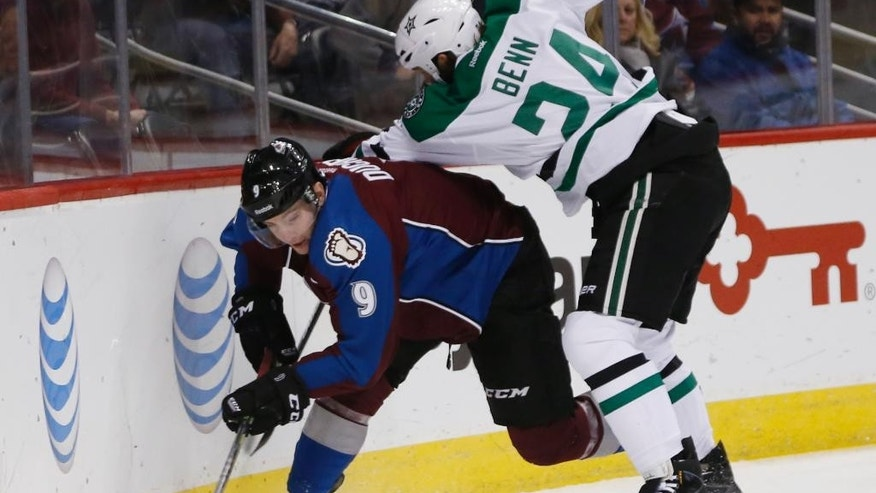 Colorado Avalanche center Matt Dcuhene, left, gets checked into the boards by Dallas Stars defenseman Jordie Benn while pursuing the puck in the first period of an NHL hockey game Saturday, Jan. 10, 2015, in Denver. (AP Photo/David Zalubowski)