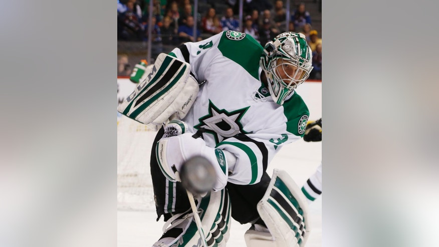 Dallas Stars goalie Kari Lehtonen, of Finland, clears the puck to the boards while facing the Colorado Avalanche in the first period of an NHL hockey game Saturday, Jan. 10, 2015, in Denver. (AP Photo/David Zalubowski)
