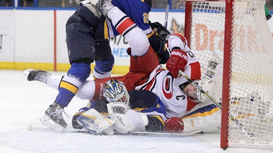 St. Louis Blues' Chris Butler (25) is tangled up with Carolina Hurricanes' Eric Staal (12) as he falls over St. Louis Blues goalie Brian Elliott (1) after scoring a goal in the first period of an NHL hockey game, Saturday, Jan. 10, 2015 in St. Louis. (AP Photo/Tom Gannam)