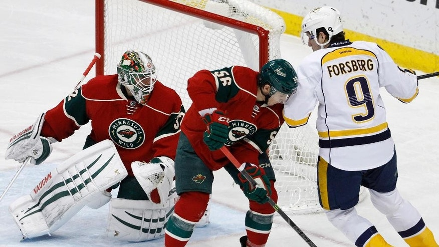 Minnesota Wild left wing Erik Haula (56), of Finland, clears the puck away from Nashville Predators center Filip Forsberg (9), of Sweden, as Wild goalie Niklas Backstrom, left, of Finland, covers the net during the first period of an NHL hockey game in St. Paul, Minn., Saturday, Jan. 10, 2015. (AP Photo/Ann Heisenfelt)
