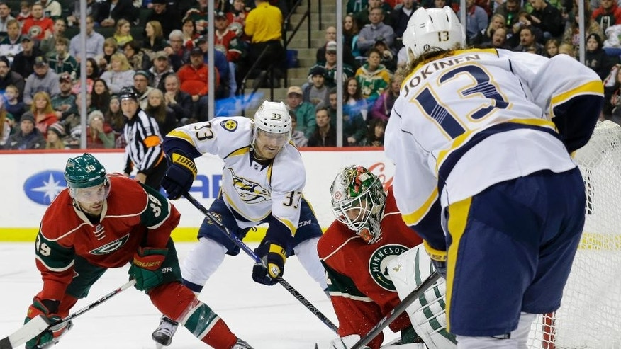 Minnesota Wild goalie Niklas Backstrom, center, of Finland, stops a shot by Nashville Predators center Olli Jokinen (13), of Finland, in front of  Wild defenseman Nate Prosser (39) and Predators center Colin Wilson (33) during the second period of an NHL hockey game in St. Paul, Minn., Saturday, Jan. 10, 2015. (AP Photo/Ann Heisenfelt)