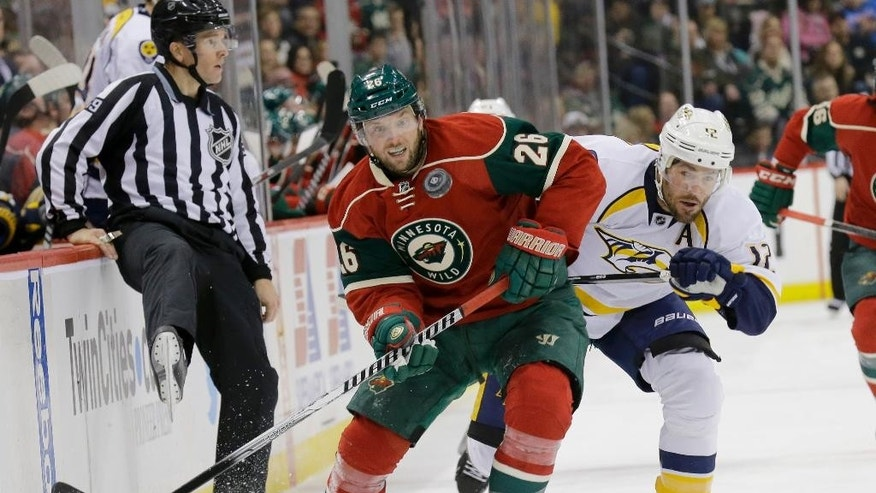 Minnesota Wild left wing Thomas Vanek (26), of Austria, and Nashville Predators center Mike Fisher (12) battle for the puck during the second period of an NHL hockey game in St. Paul, Minn., Saturday, Jan. 10, 2015. (AP Photo/Ann Heisenfelt)