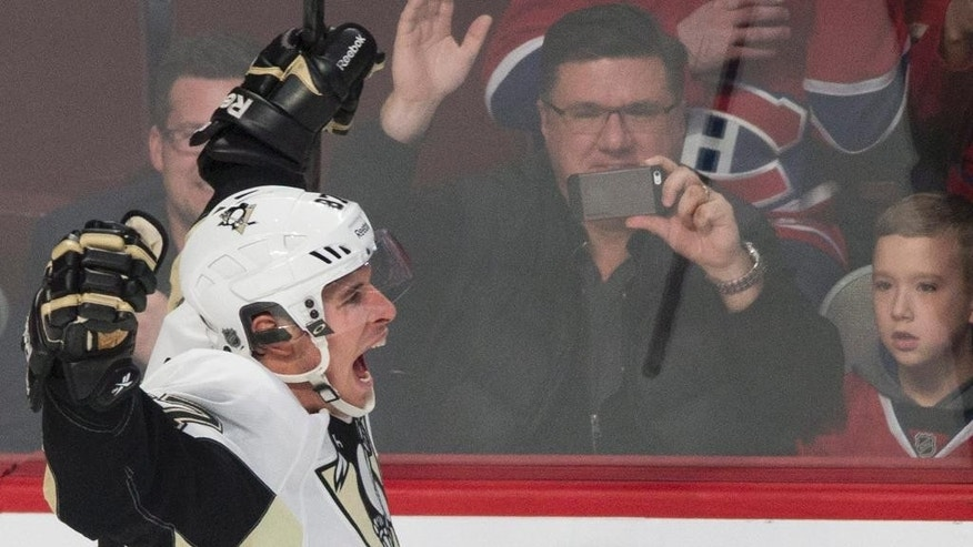 Pittsburgh Penguins' Sidney Crosby celebrates after scoring the winning goal against the Montreal Canadiens during overtime of an NHL hockey game Saturday, Jan. 10, 2015, in Montreal. The Penguins won 2-1. (AP Photo/The Canadian Press, Graham Hughes)