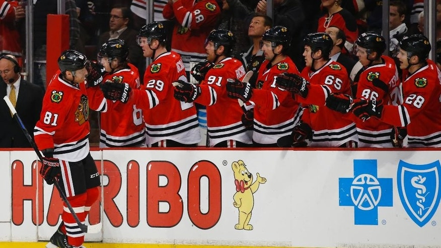 Chicago Blackhawks right wing Marian Hossa (81) celebrates with teammates after scoring against the Minnesota Wild during the first period of an NHL hockey game in Chicago, Sunday, Jan. 11, 2015. (AP Photo/Kamil Krzaczynski)