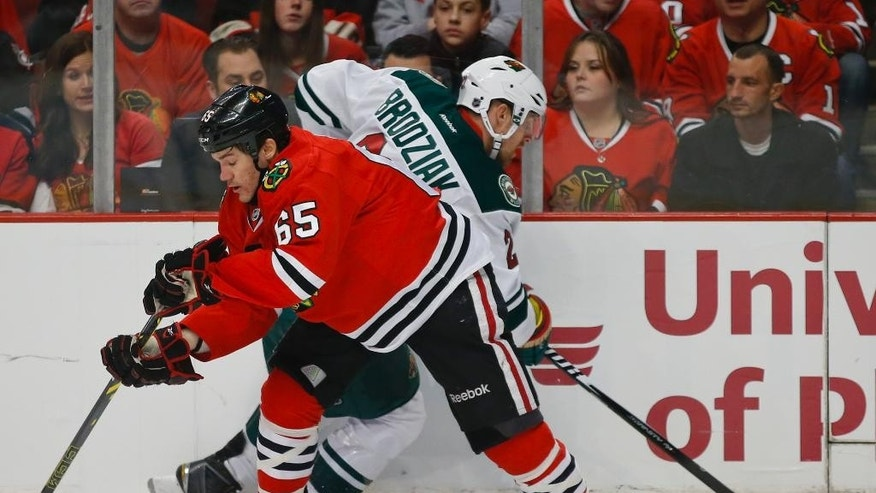 Chicago Blackhawks center Andrew Shaw (65) battles for the puck with Minnesota Wild center Kyle Brodziak (21) during the first period of an NHL hockey game in Chicago, Sunday, Jan. 11, 2015. (AP Photo/Kamil Krzaczynski)